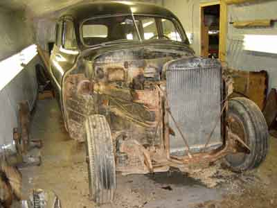 Image of 1949 Henney packard hearse in the shop, with the front end removed to show the in-line 8 cylinder engine.